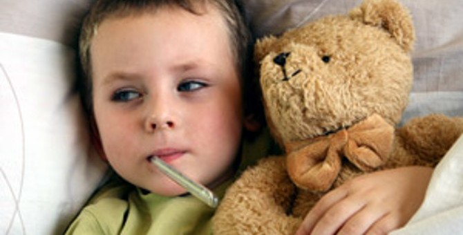 670_Sick-child-with-thermomenter-cuddling-bear-in-bed